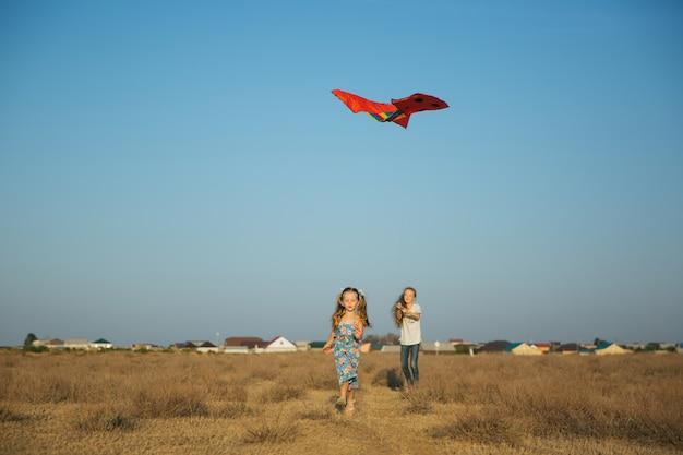 Schwestern laufen und spielen mit drachen auf dem feld