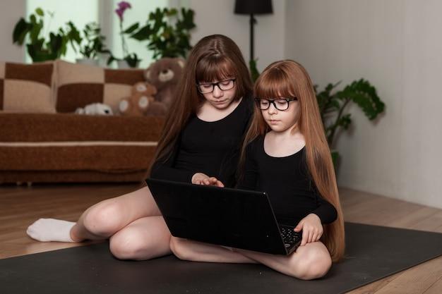 Schwestern von kleinen mädchen halten zu hause eine online-gymnastikstunde ab