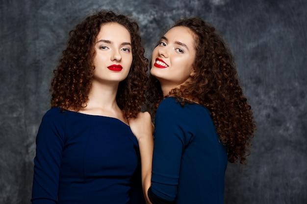 Schwestern zwillinge lächeln auf grau