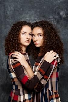 Schwestern zwillinge posieren auf grau