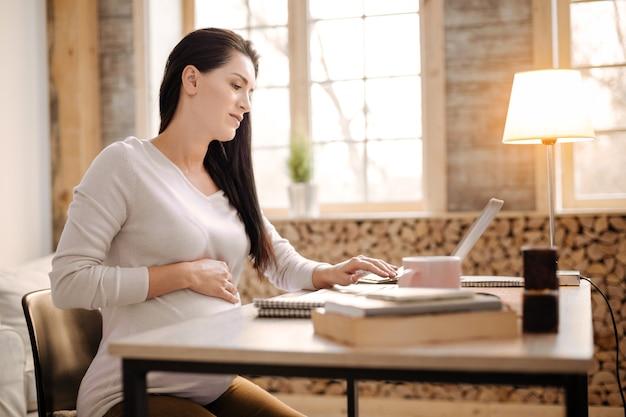 Schwierige arbeit. bezaubernde ernsthafte schwangere frau, die im profil sitzt, während laptop verwendet und hand auf bauch legt