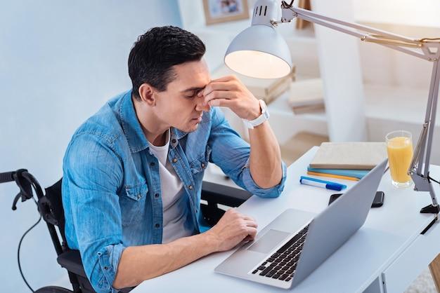 Schwierige aufgabe. nachdenklicher ungültiger mann, der die augen geschlossen hält und die arme auf den tisch legt, während er an seinem arbeitsplatz sitzt