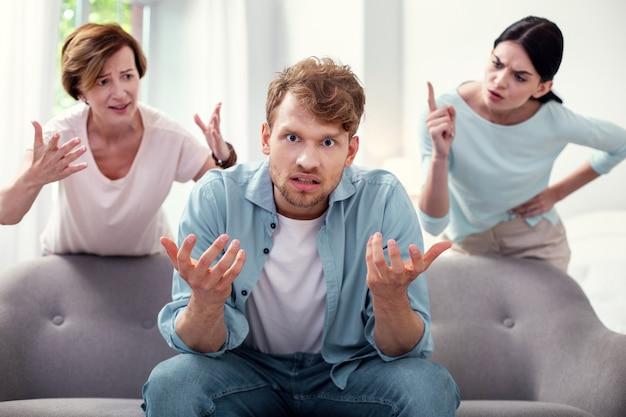 Schwierige familiäre situation. deprimierter freudloser mann, der sich gestresst fühlt, während er dem streit zwischen frauen lauscht