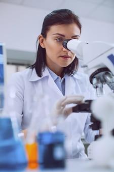 Schwierige forschung. konzentrierte kluge wissenschaftlerin, die mit ihrem mikroskop arbeitet und eine uniform trägt
