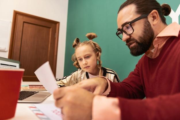 Schwieriges material. nettes blondes mädchen mit armbändern auf ihrer hand, die konzentriert lesen, während sie neue wörter lesen