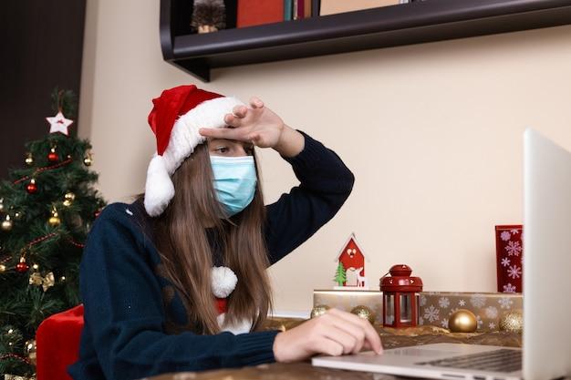 Schwierigkeiten bei online-glückwünschen. ein junges mädchen in einem weihnachtsmannhut und einem blauen pullover in einer medizinischen maske sitzt in der nähe eines laptops. das zimmer ist festlich eingerichtet. weihnachten während des coronavirus