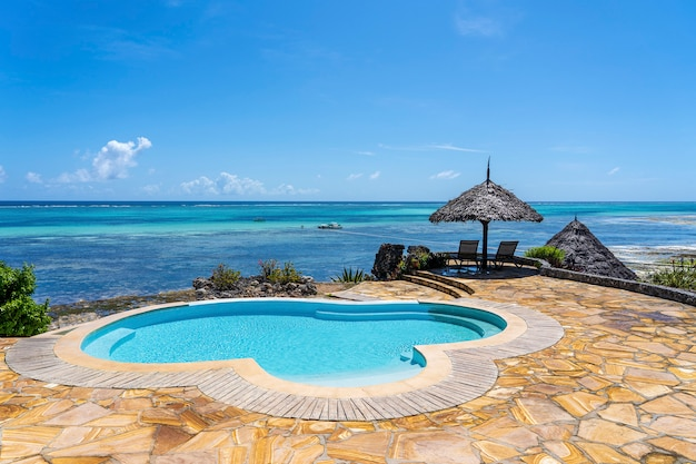 Schwimmbad und strohschirm an einem tropischen strand nahe dem meer in sonnigem tag