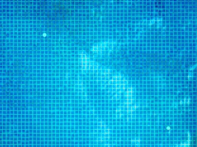Schwimmbadboden mit kleinen quadratischen blauen mosaikfliesen mit baumschatten auf klarer wasseroberfläche