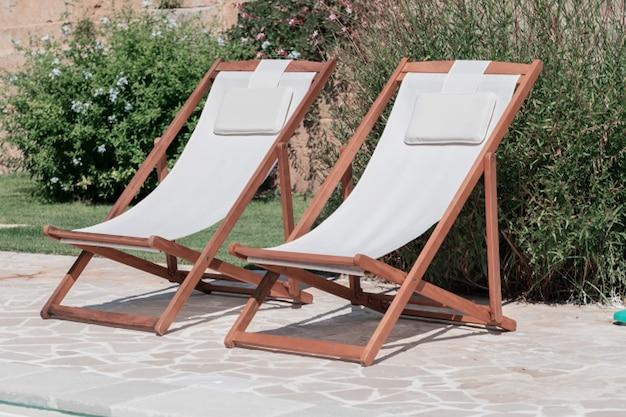 Schwimmbecken mit klarem blauem wasser und zwei sonnenliegen an sonnigen tagen in einem hof