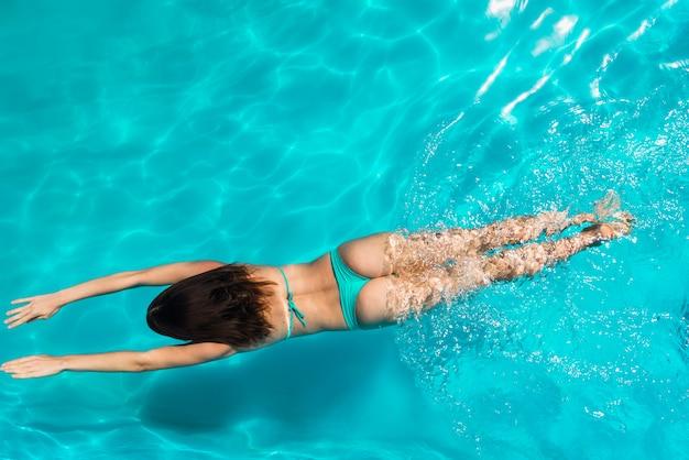 Schwimmen der erwachsenen frau unter hellem klarem wasser