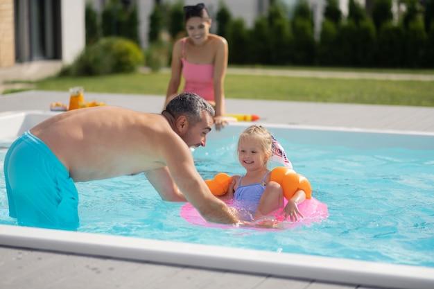 Schwimmen in der nähe von papa. fröhliche schöne schöne tochter, die sich beim schwimmen in der nähe von papa glücklich fühlt