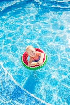 Schwimmen, sommerferien - reizendes lächelndes mädchen, das im blauen wasser mit rettungsringwassermelone spielt.