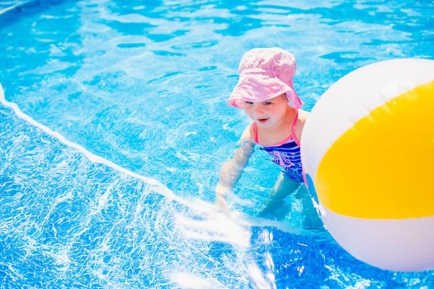Schwimmen, sommerferien - reizendes lächelndes mädchen im rosa hut und im blauen badeanzug, die im blauen wasser mit aufblasbarem mehrfarbigem ball in einem pool spielen