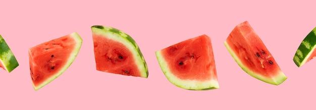 Schwimmende, fliegende, schwebende geschnittene frische wassermelone auf rosa hintergrund. sommerfrüchte, beeren. trendiges, minimalistisches kreatives essen. konzept des wassermelonentages-august 3.