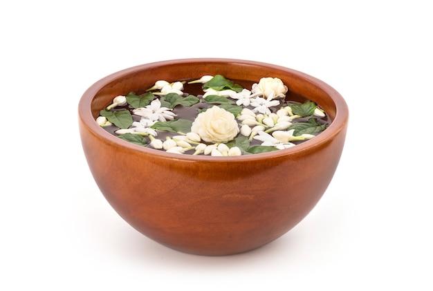 Schwimmende jasminblüten und grüne blätter im wasser auf holzschale lokalisiert auf weiß.