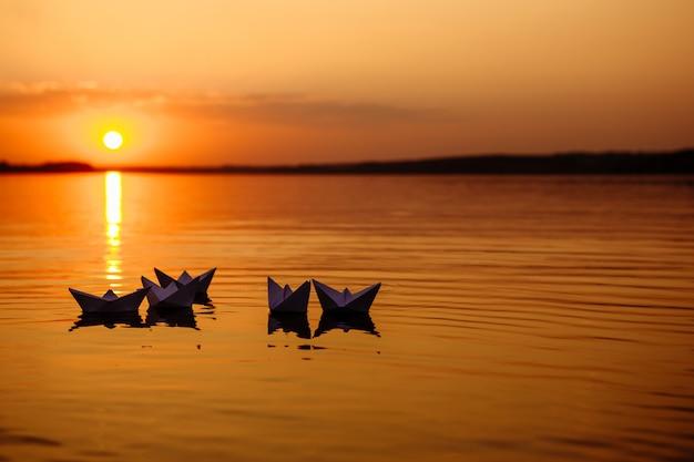 Schwimmende papierboote auf dem wasser bei sonnenuntergang. papierschiffchen. origami.