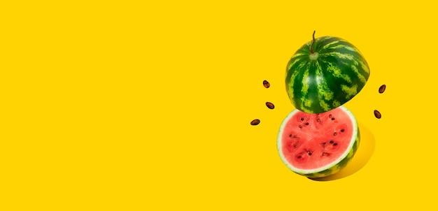 Schwimmende, schwebende geschnittene frische wassermelone mit einem schwanz, samen auf gelbem hintergrund. sommerfrüchte, beeren. kräftige farbe. trendige, minimale schatten. kreatives essen. konzept des wassermelonentages-august 3.platz kopieren