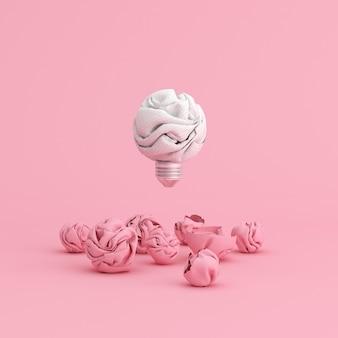 Schwimmende zerknitterte papierglühbirne auf rosa hintergrund.