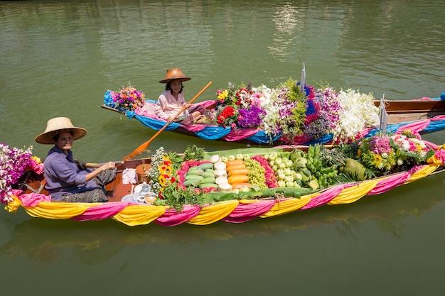 Schwimmender markt mit obst, gemüse und verschiedenen artikeln, die von kleinen booten verkauft werden