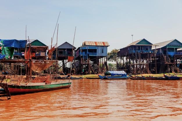 Schwimmendes fischerdorf kampong phluk während der dürrezeit, häuser auf stelzen, menschen und booten