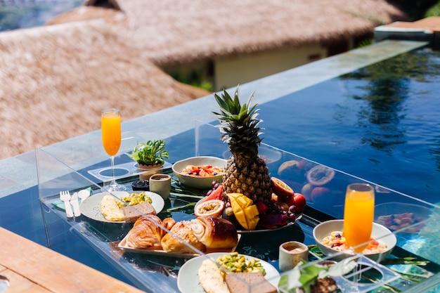 Schwimmendes frühstück in einer fantastischen hotelvilla im blauen pool