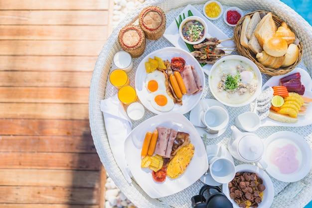 Schwimmendes frühstück in tablett mit spiegelei-omelett-wurst-schinken-brot-fruchtmilch-saft-kaffee