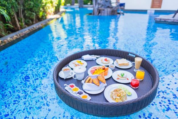 Schwimmendes frühstücksset in tablett mit spiegelei-omelett-wurst-schinkenbrot-fruchtmilch-saft-kaffee