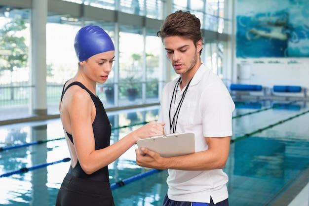 Schwimmer, der zeiten mit ihrem trainer am pool bespricht