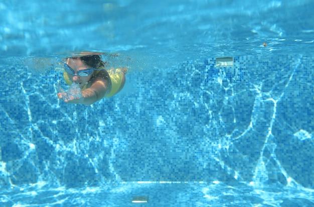 Schwimmer des jungen mädchens, der unter wasser im pool schwimmt und spaß hat, jugendlichtauchen unter wasser, familienurlaub, sport und eignungskonzept