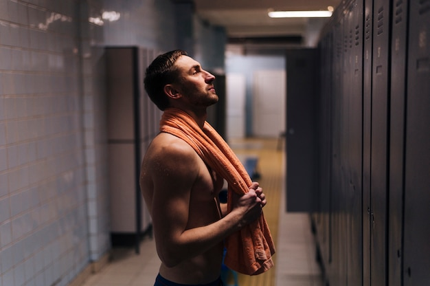Schwimmer des jungen mannes der seitenansicht im umkleideraum