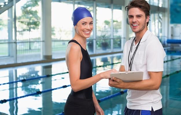 Schwimmer lächelt in die kamera mit ihrem trainer am pool