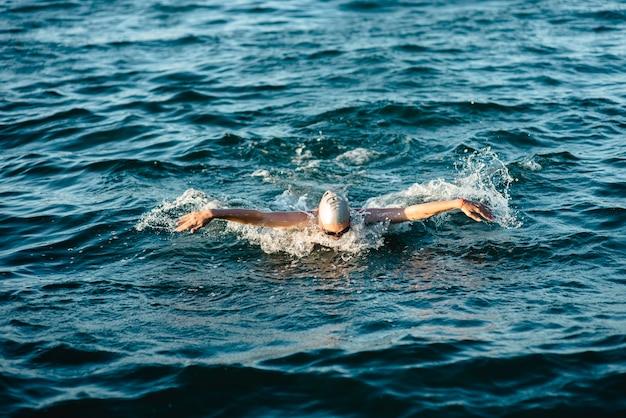 Schwimmer mit mütze und schutzbrille im wasser schwimmen