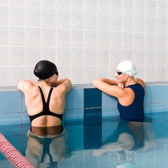 Schwimmerfreunde, die im pool sich entspannen