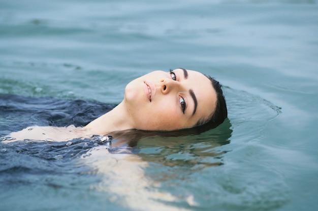 Schwimmerin, die wassergymnastik im see tut