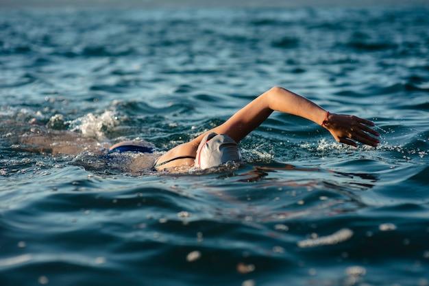 Schwimmerin mit mütze und schutzbrille, die im wasser schwimmen