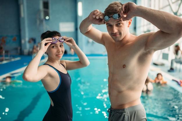 Schwimmerinnen und schwimmer setzen beim training im schwimmbad eine schutzbrille auf. aqua aerobic training, wassersport