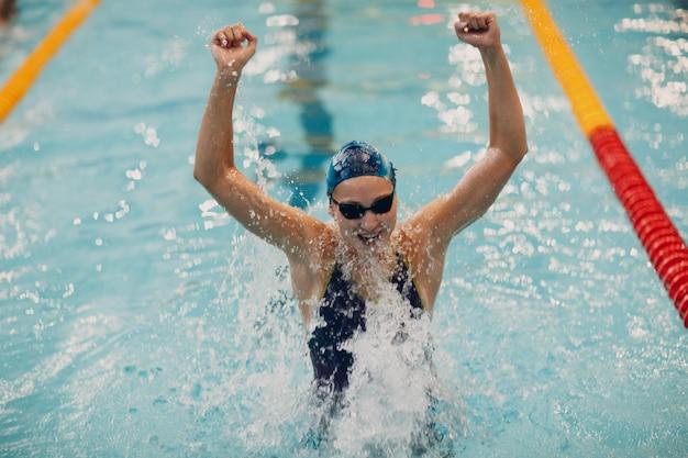 Schwimmerporträtfreude der jungen frau freut sich über den sieg bei schwimmwettbewerben im schwimmbad. konzept gewinnen.