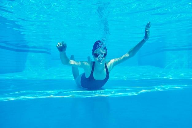 Schwimmkappe des schwimmers des jungen mädchens unter wasser im pool
