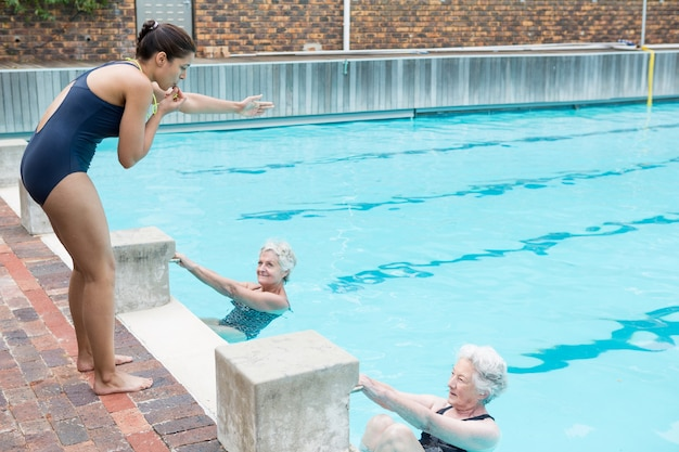 Schwimmlehrerin, die ältere frauen am pool unterstützt