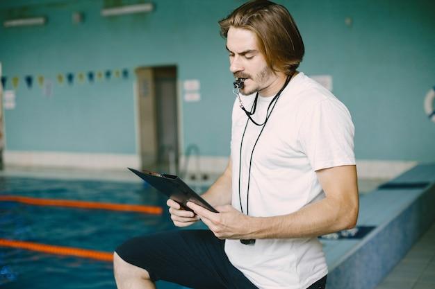 Schwimmtrainer, der am pool steht. schwimmaufzeichnungen überprüfen. zwischenablage halten.