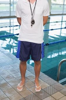 Schwimmtrainer, der am pool steht