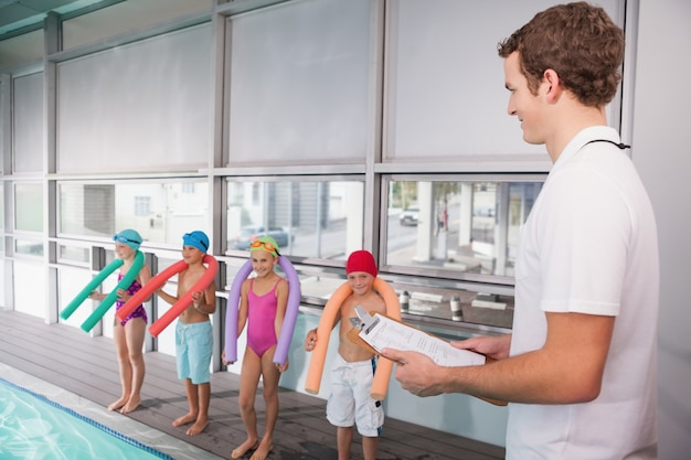 Schwimmtrainer, der klemmbrett pool hält