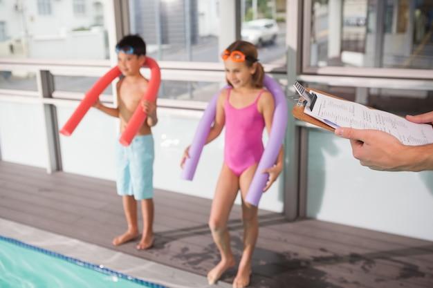 Schwimmtrainer, der klemmbrett poolside hält