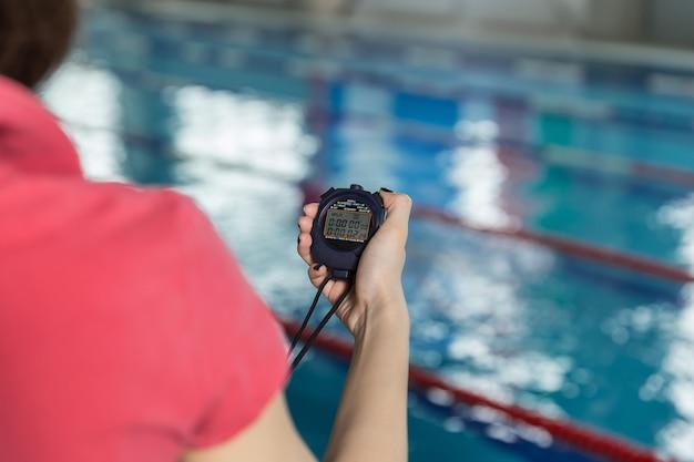 Schwimmtrainer mit stoppuhr am pool im freizeitzentrum.