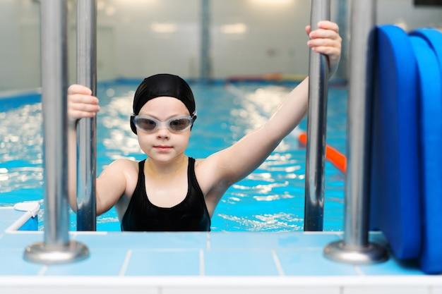 Schwimmunterricht für kinder im pool - schönes hellhäutiges mädchen schwimmt im wasser