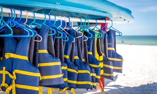 Schwimmwesten und boote auf st.pete setzen in florida, usa auf den strand