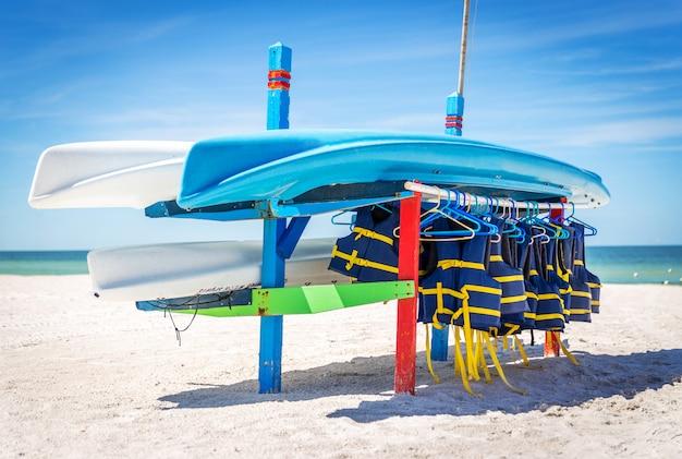 Schwimmwesten und boote auf st.pete setzen in florida, usa auf den strand.
