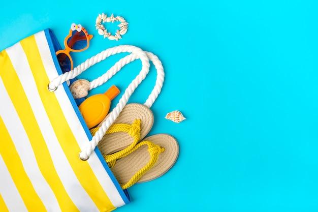 Schwimmzubehör - trendige strandtasche mit streifen sonnencreme, herzförmige brille, gelber flip-flop, muscheln auf blauem hintergrund flache lage