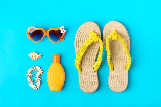 Schwimmzubehör - trendiger sonnenschutz, herzförmige brille, flip flop, handfläche, muscheln, tablette auf blauem hintergrund flache lage