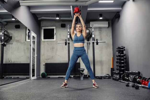 Schwingen sie das training mit einer kesselglocke, um die gesamten körpermuskeln zu pumpen. eine vorderansicht einer sexy frau in sportbekleidung und in guter körperlicher form beim heben von gewichten in einem indoor-fitnessstudio. fitness herausforderung